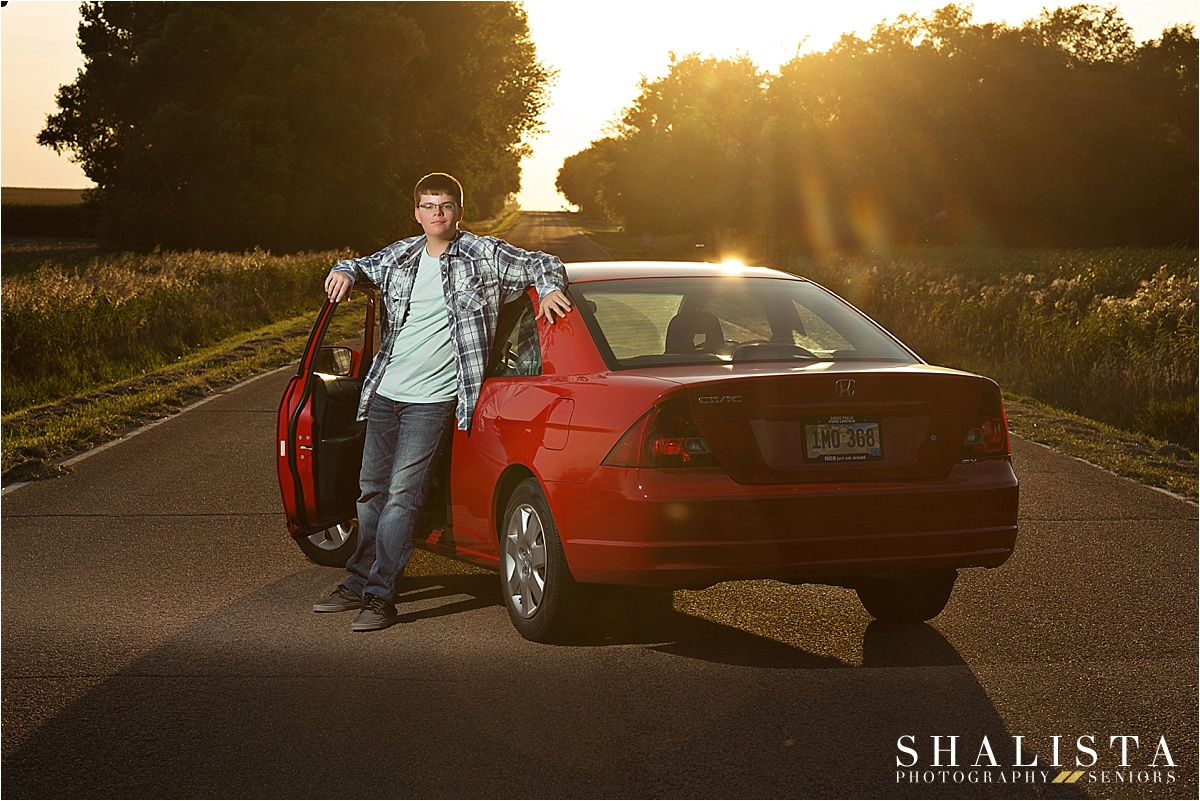 Senior boy with red car on road.