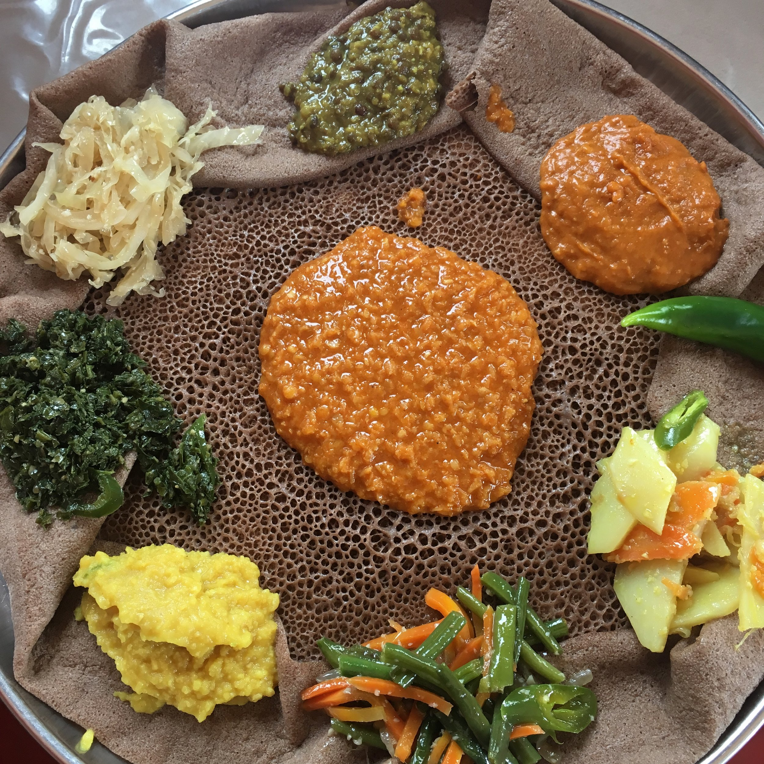 Yetsom beyaynetu, a traditional tapas-like style of vegan stews and dishes traditionally eating during fasting periods. Served dark injera.