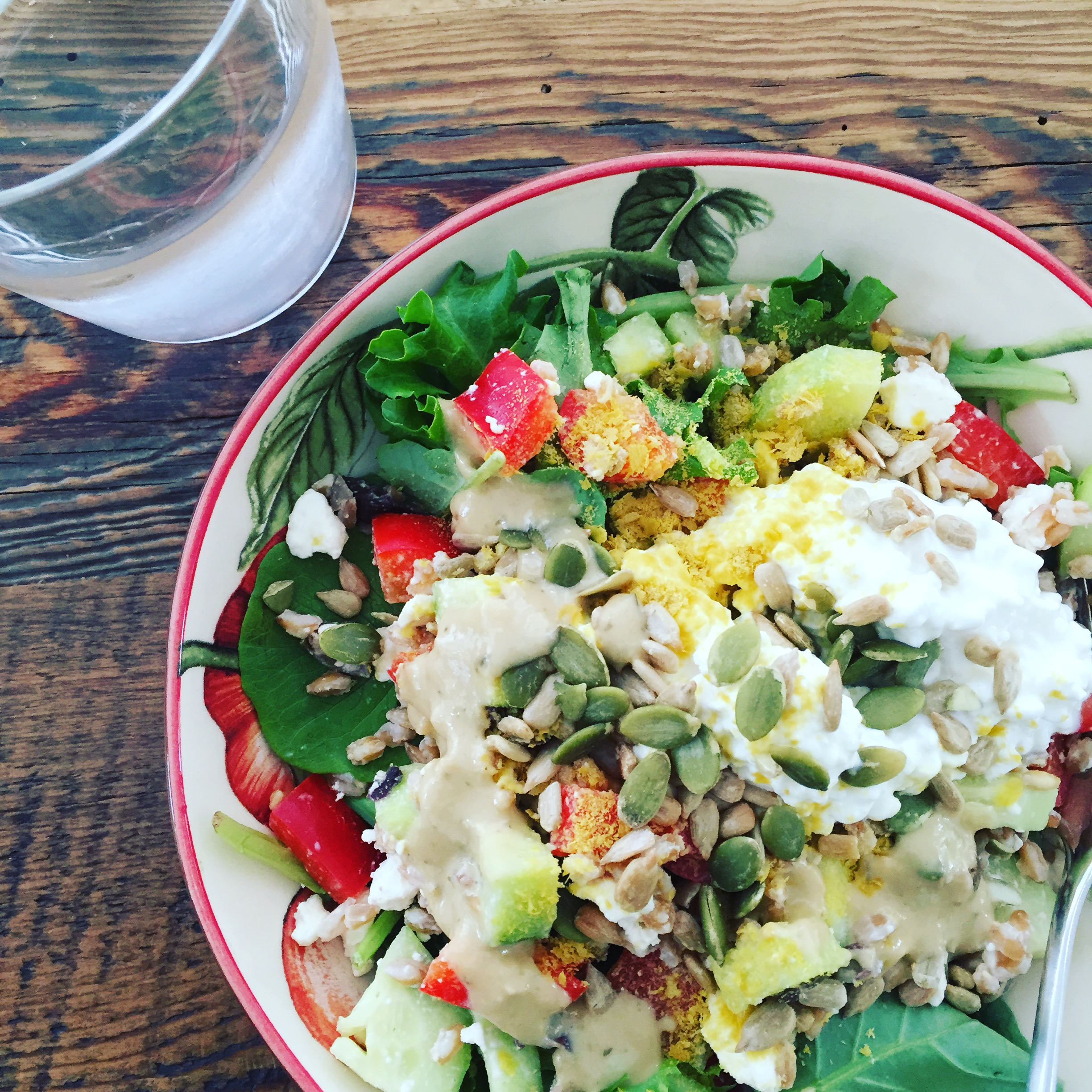 Farro Salad on a bed of lettuce with cottage cheese, sunflower seeds, pumpkin seeds, nutritional yeast and goddess dressing.