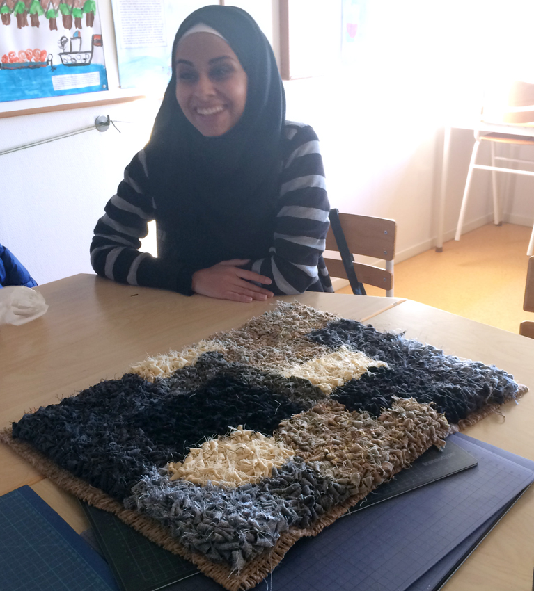 Hylana and her beautiful carpet made of fabric strips.
