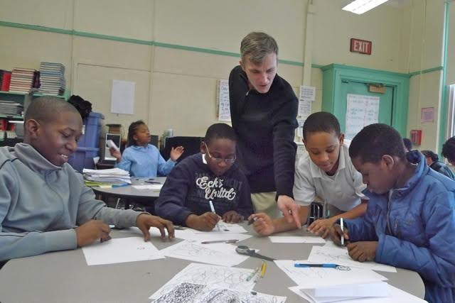 James Hobin reviewing artwork with students at the Nathan Hale School on Fort Hill in Roxbury.
