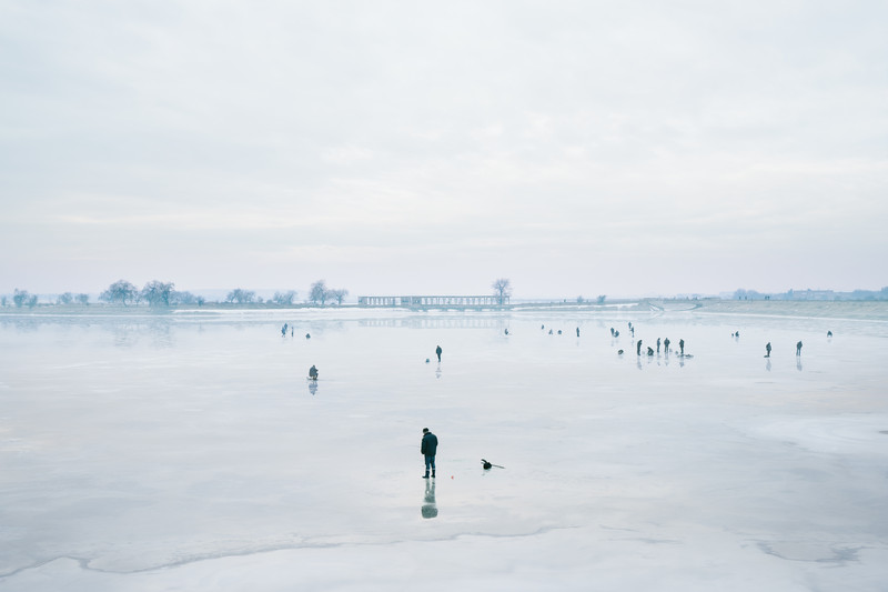 At the entrance to Lacul Morii in Bucharest, men from the area converge to fish on the ice.