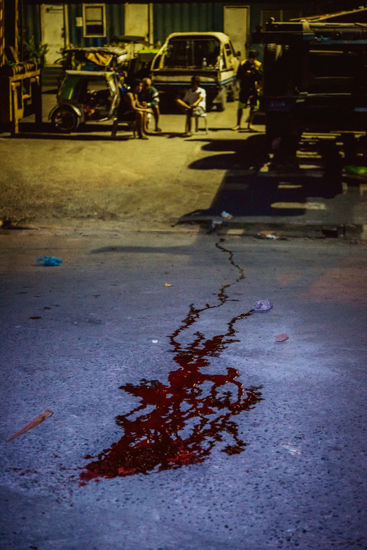 The blood and brains of Nikki Mercado, 27, trickle downhill into a gutter. Mercado's body was found dead with several gunshot wounds without any leads on a suspect. His death marks another case in the growing list of extrajudicial killings and forced disappearances that began during President Duterte's War on Drugs in 2016.  NAVOTAS, MANILA. 2018.
