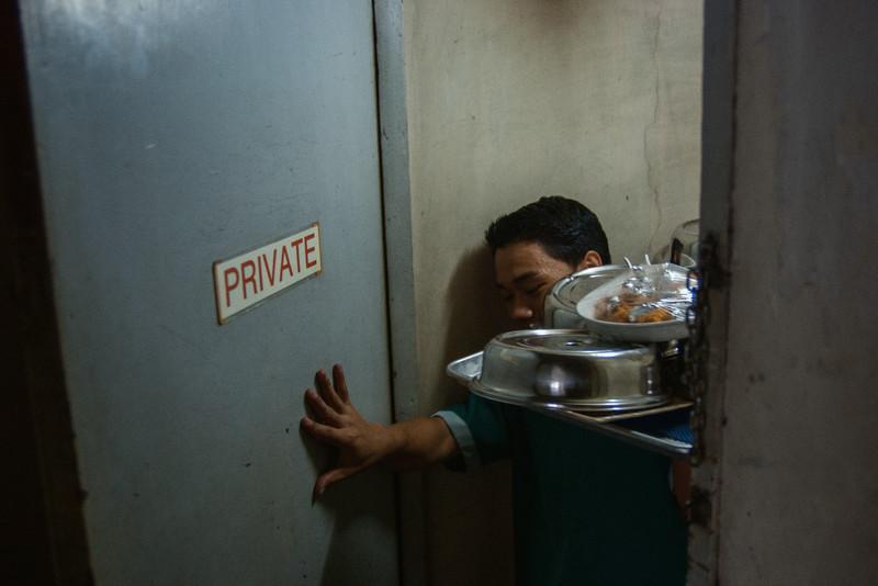 A waiter enters the service entrance into the penthouse of the Manila Manor Hotel.  MALATE, MANILA. 2007.