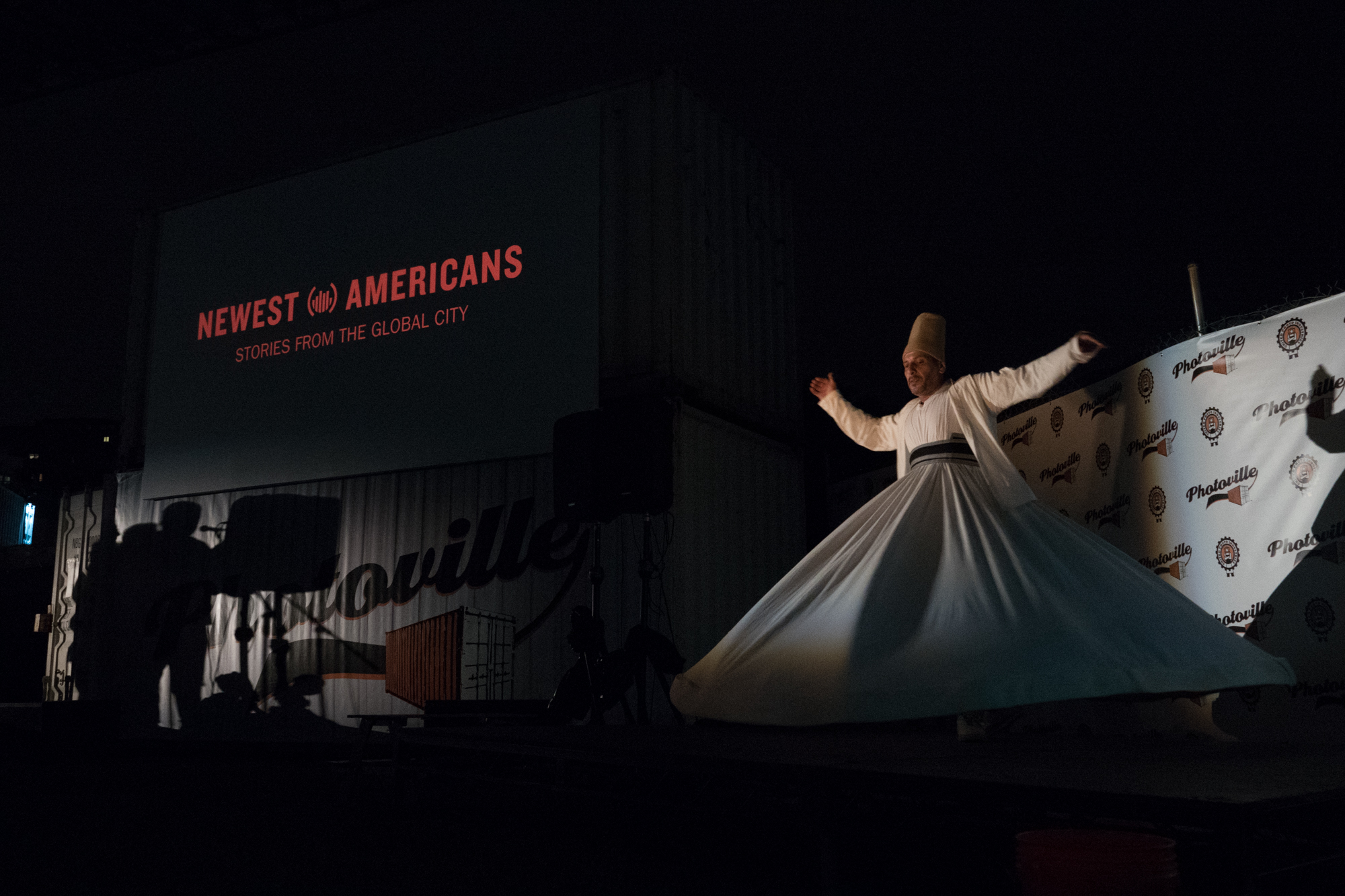 A whirling dervish spins to traditional Syrian music at the end of Newest Americans' Opening Night presentation at Photoville 2017. (Photo by Stephanie Khoury)