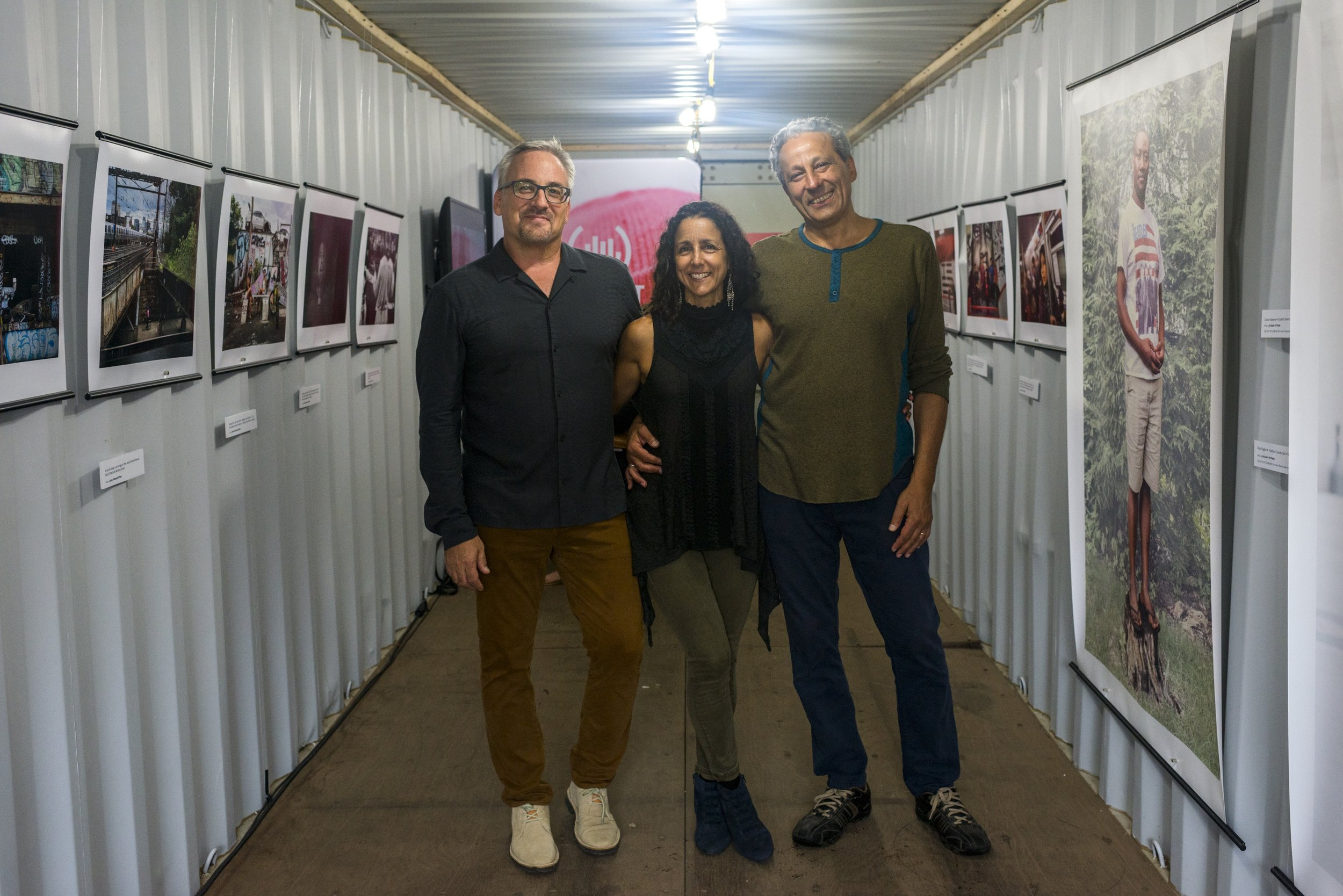 Newest Americans partners Tim Raphael, Julie Winokur, and Ed Kashi smile for the camera in our container exhibit. (Photo by Gareth Smit)