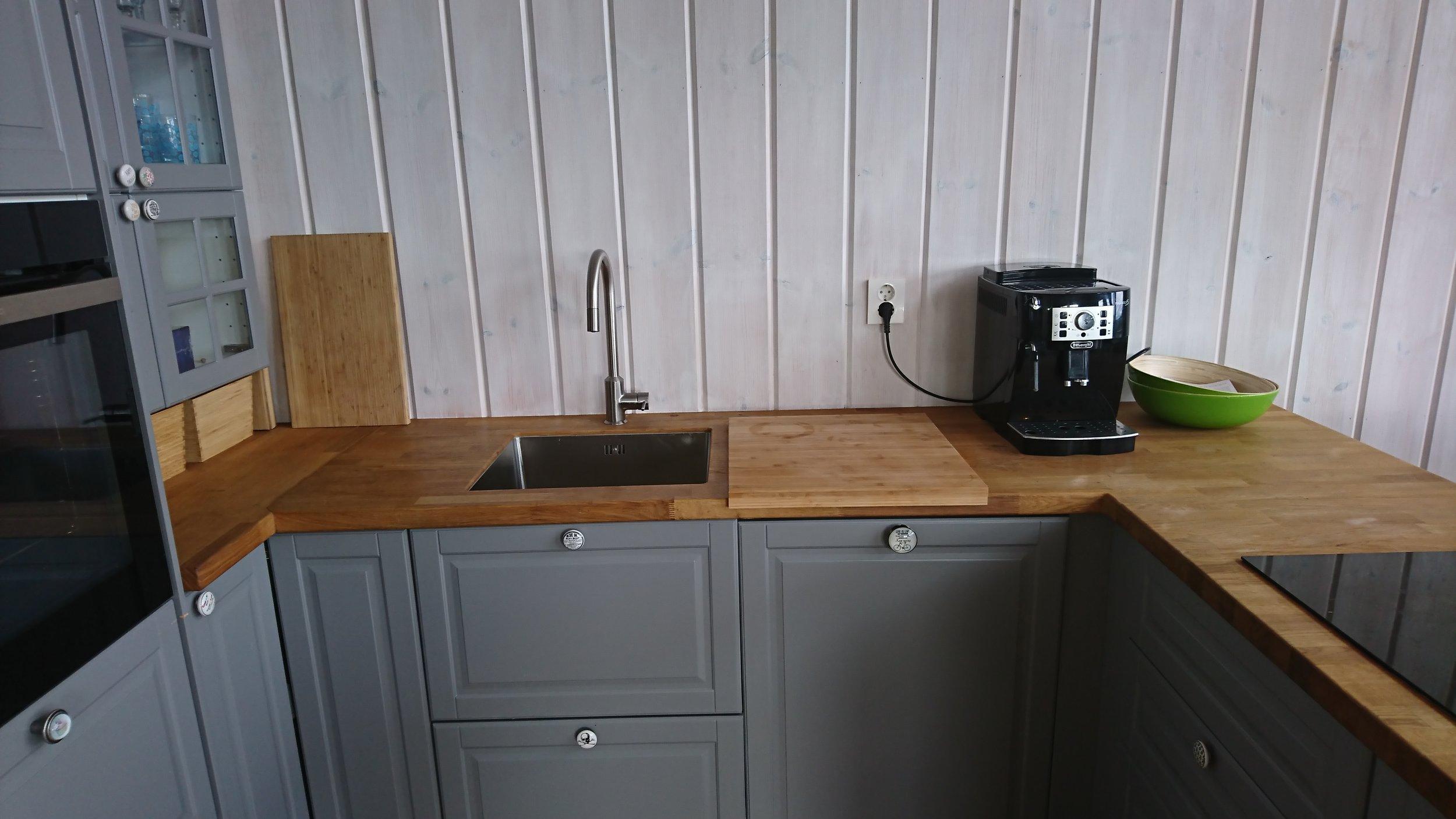 """På kjøkkenet er oppvaskmaskin under kaffemaskinen. Bruksanvisning til kaffemaskinen ligger i den grønne skålen. Tuten på vannkranen kan """"trekkes ut"""" slik at det blir litt lettere å skylle i vaskekummen. Under vaskekummen er søppel og oppvask ting. Det er også en atomatisk vannstopp som stenger vannet til oppvaskmaskinen hvis den registrere vannlekasje."""