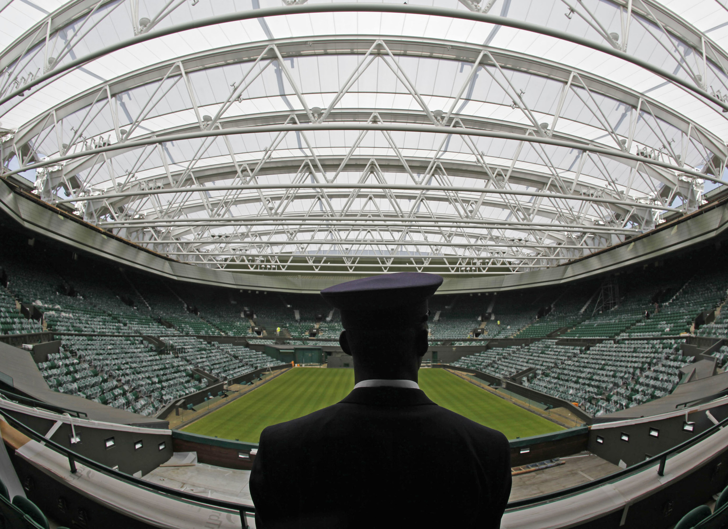 A security guard stands underneath the new Centre Court retractable roof at the All England Lawn Tennis Club in London (Courtesy of Reuters)
