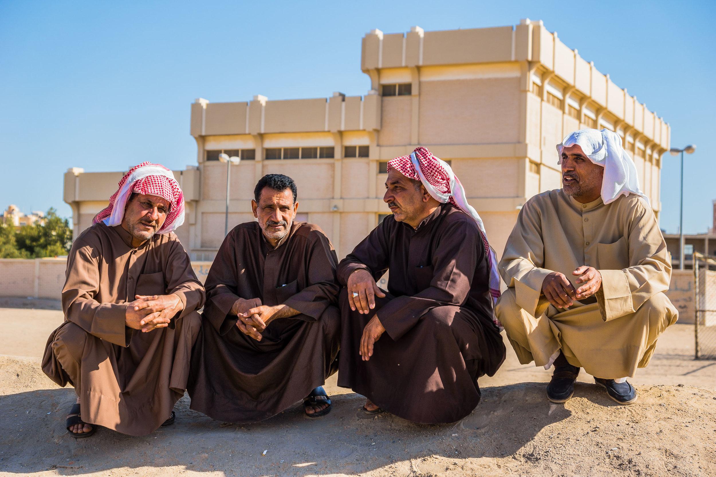 Men sit on the roadside in the winters sun. Kuwait, 2016