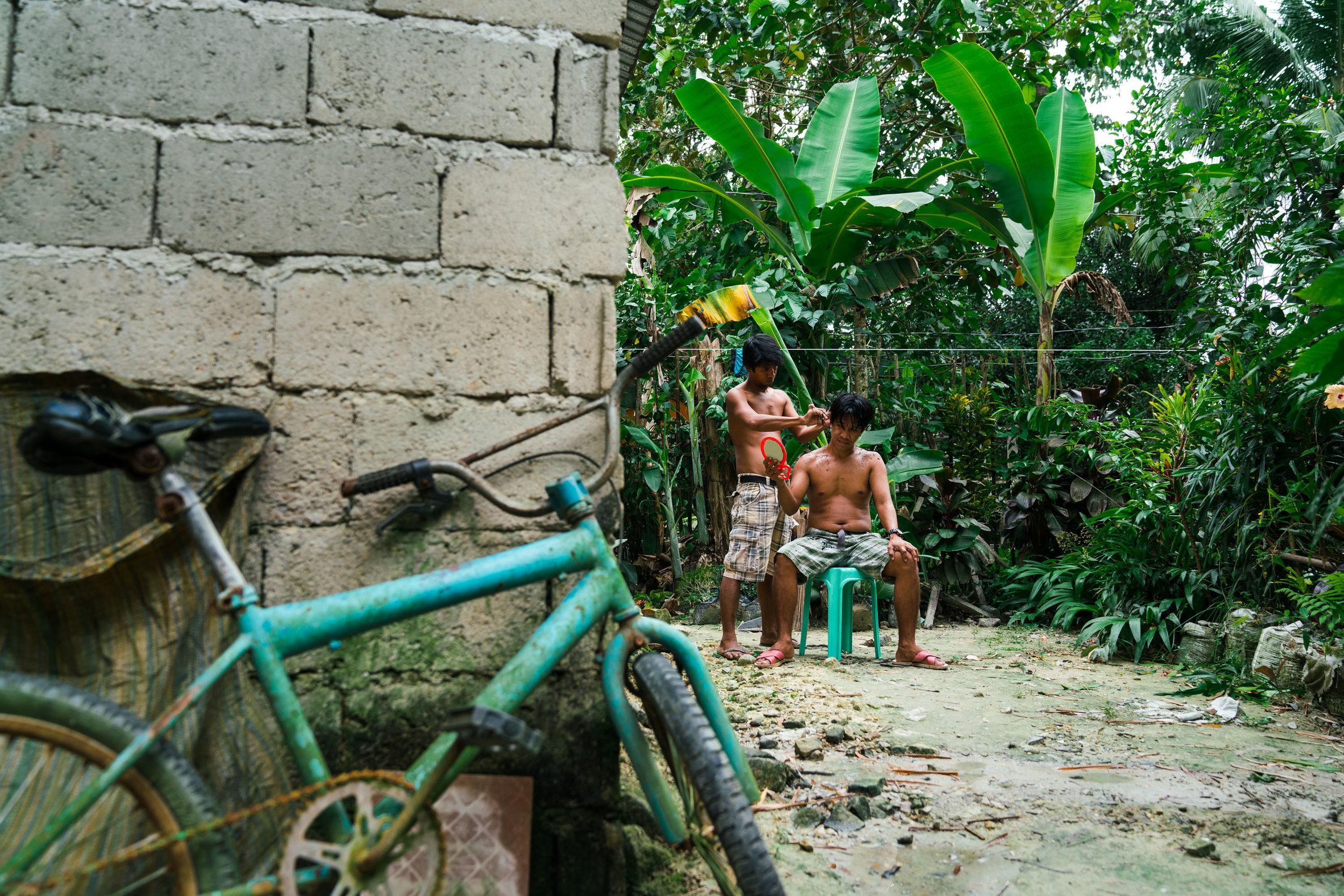 A man cuts his friends hair in his garden. Port Barton, Palawan. Philippines, 2018
