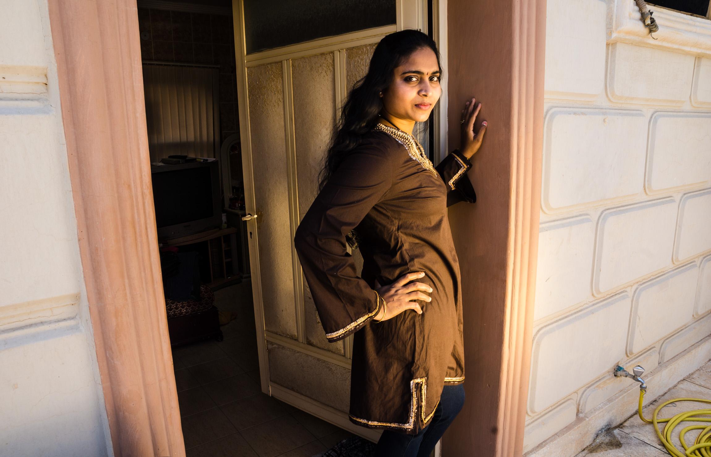 Indian maid standing in the doorway to her bedroom. Kuwait City, Kuwait. 2014
