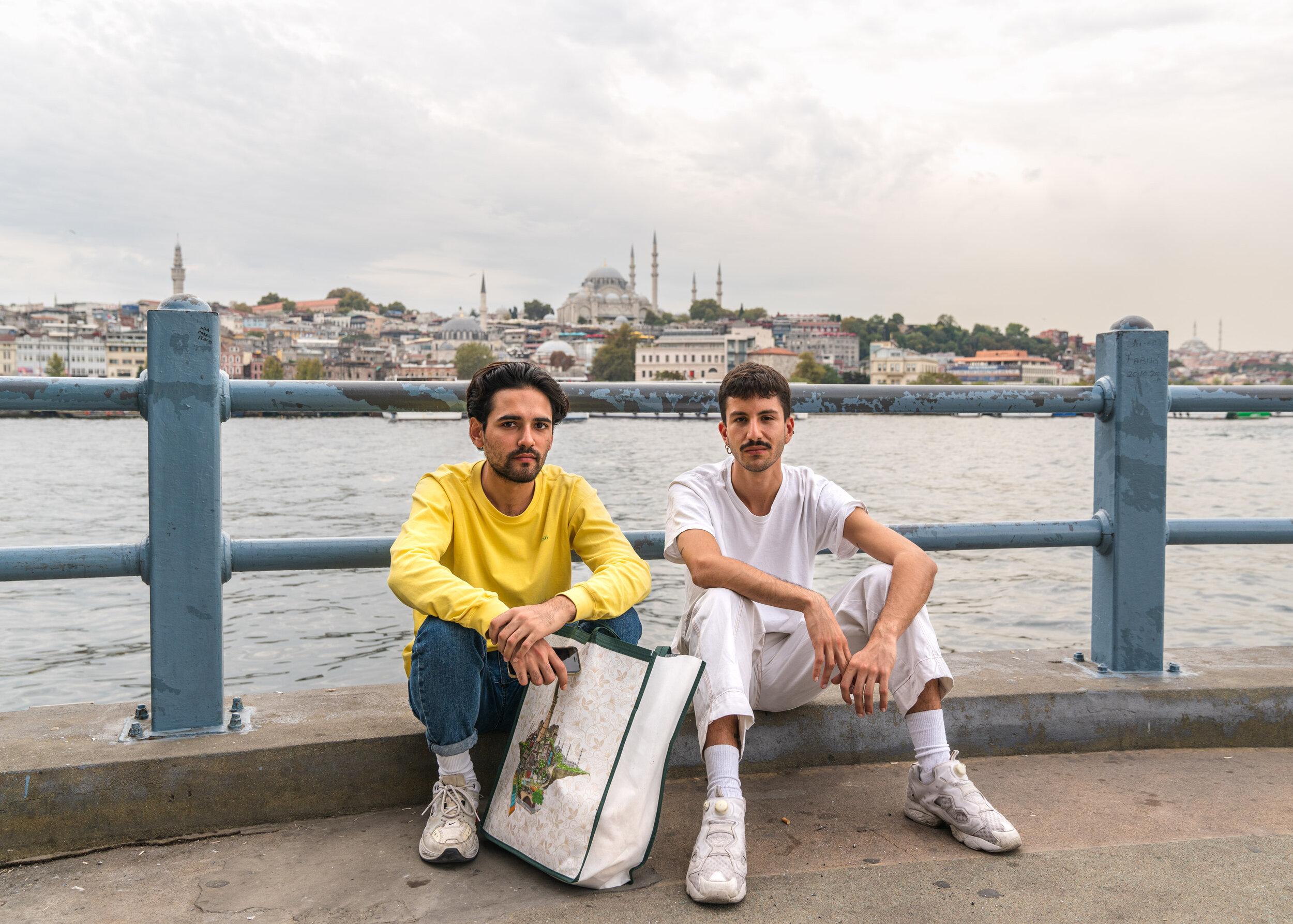 Two men sit chatting under the Galata Köprüsü bridge, Istanbul. Turkey 2019