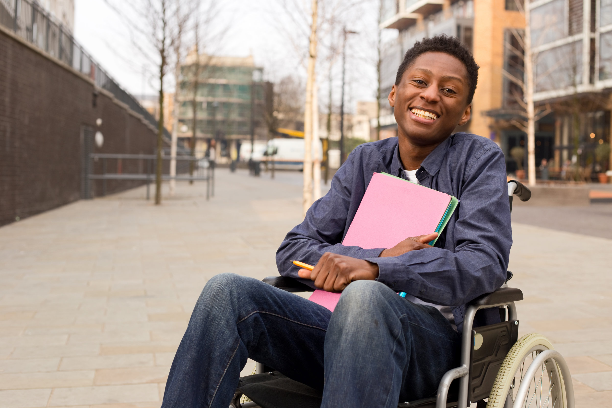 Happy young disabled man in a wheelchair holding folders.