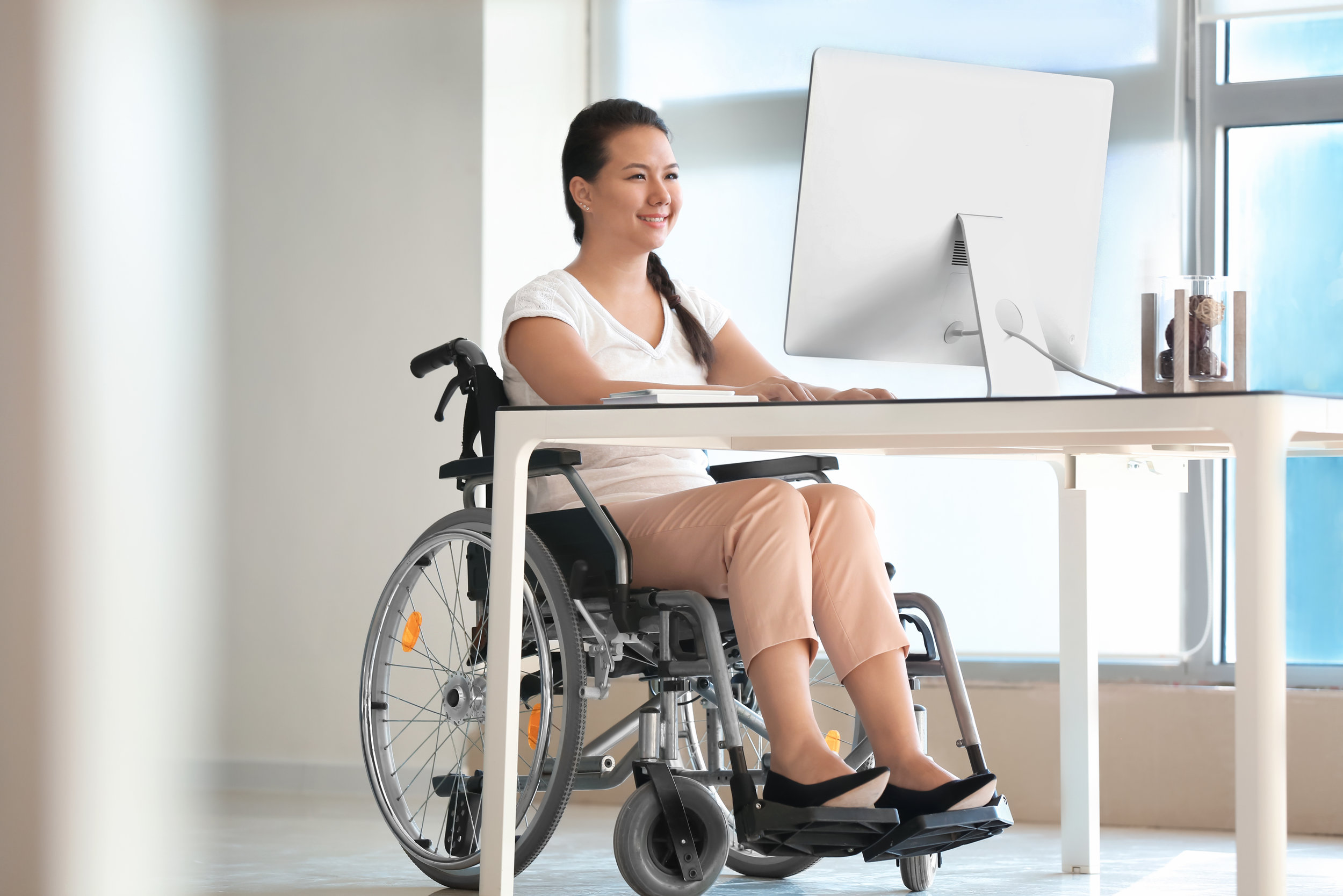 Asian woman in wheelchair working with computer in office.
