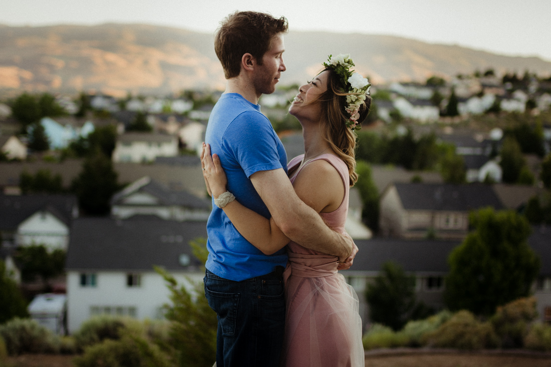 Husband and wife hugging each other on top of a hill in Reno, NV