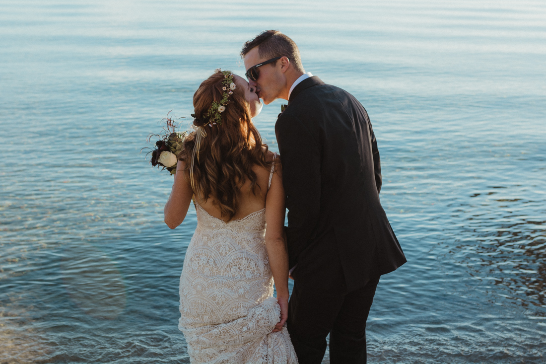 Incline village beach wedding couple kissing on the dock photo