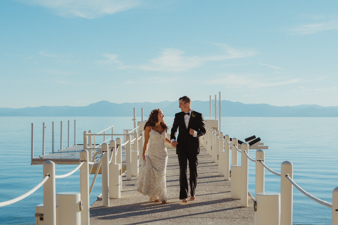 Incline village beach wedding couple running on the dock photo