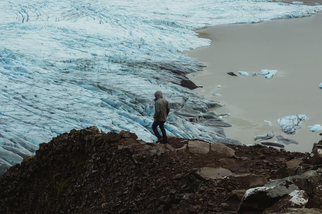 Guy walking by a glacier in Iceland