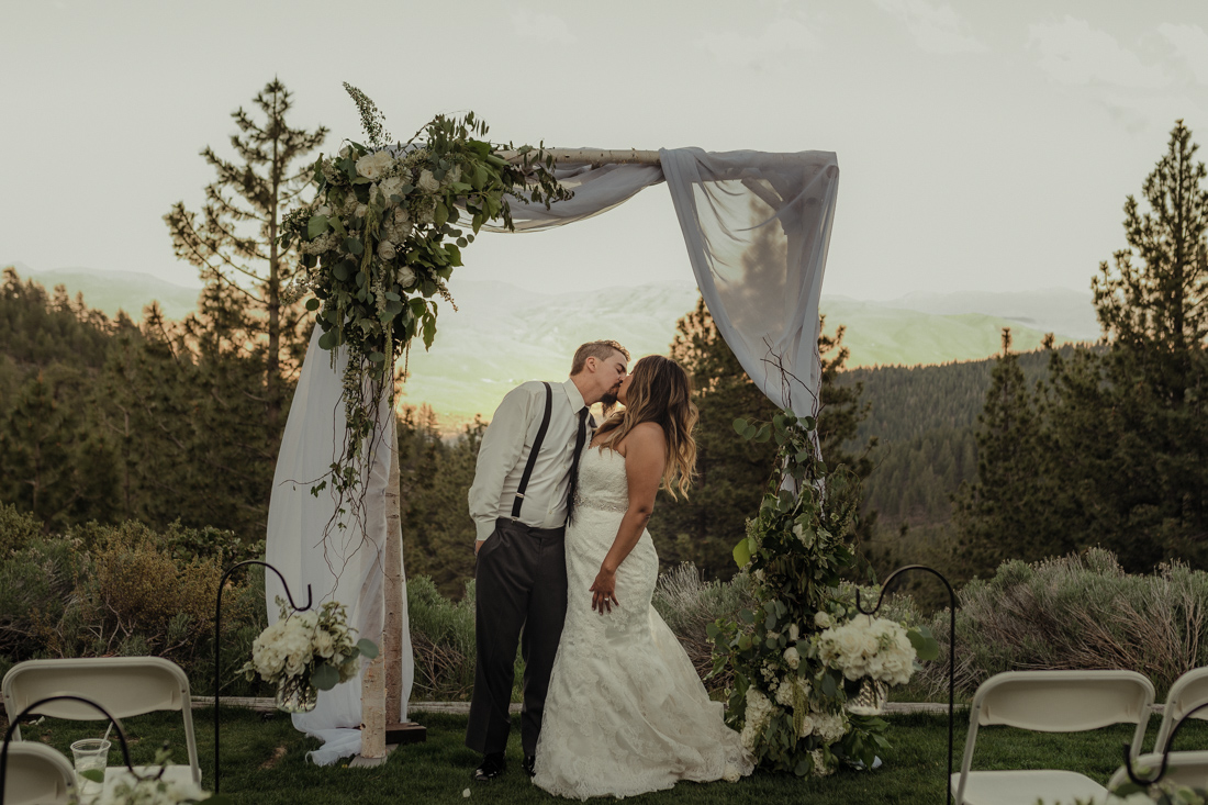Tannenbaum Wedding couple kissing under a flower arch photo