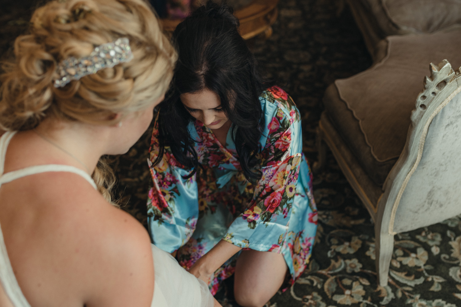 Wedgewood Sequoia Mansion wedding MOH putting on brides shoes photo