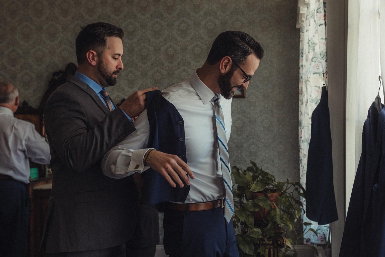Nevada City Wedding national hotel groom putting on his coat photo