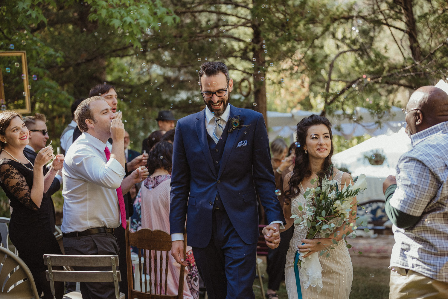 Nevada City wedding bride and groom walking down the aisle as guests blow bubbles photo