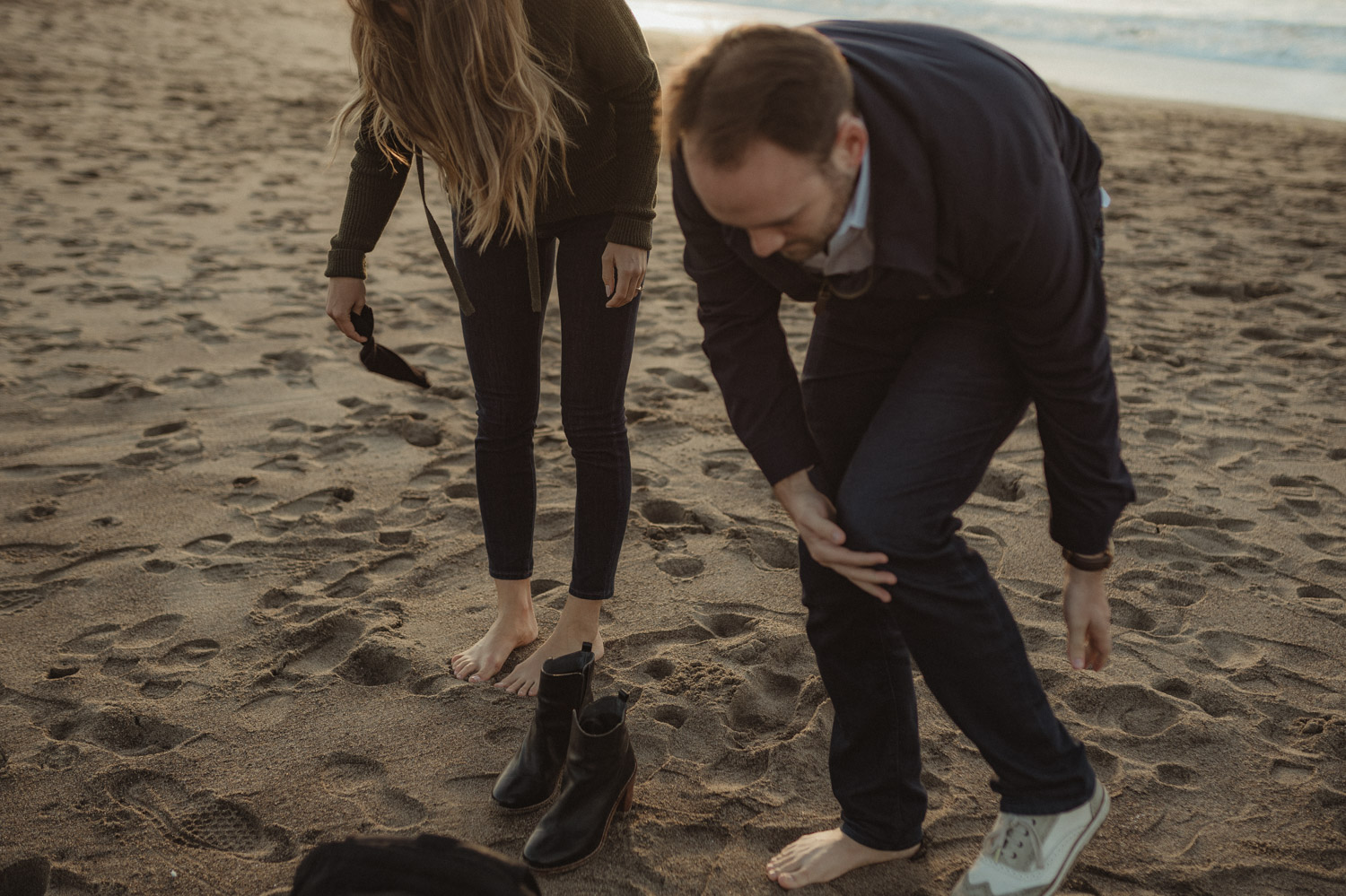 San Francisco engagement couple taking off their shoes at Baker Beach photo