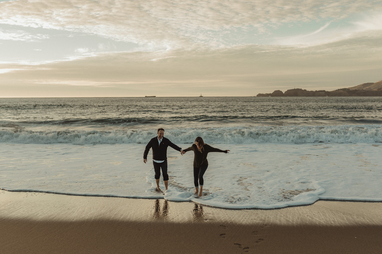 San Francisco engagement couple walking by the shore at Baker Beach photo