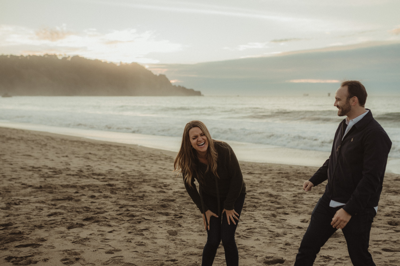 San Francisco engagement couple laughing at Baker Beach photo