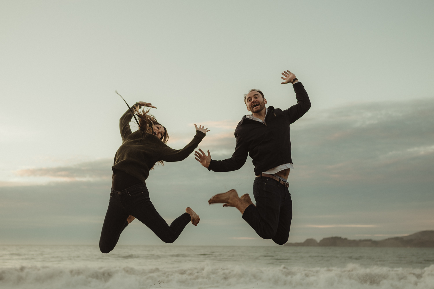 San Francisco engagement couple jumping in the air at Baker Beach photo