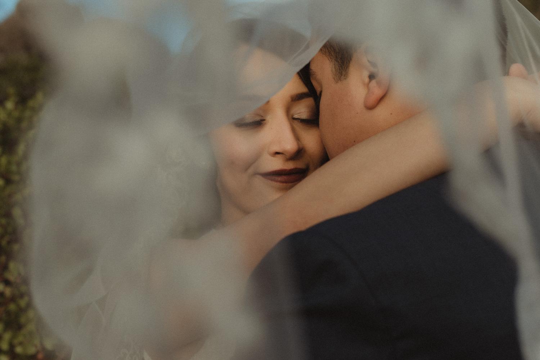 Logan Shoals elopement couple hugging under the veil photo