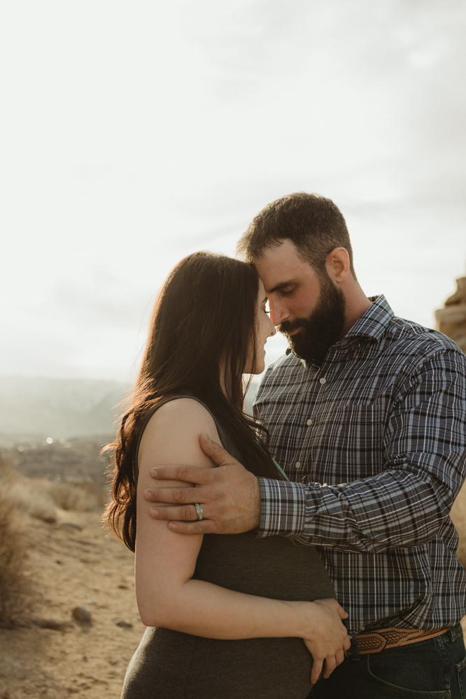 Desert maternity session couple touching foreheads photo