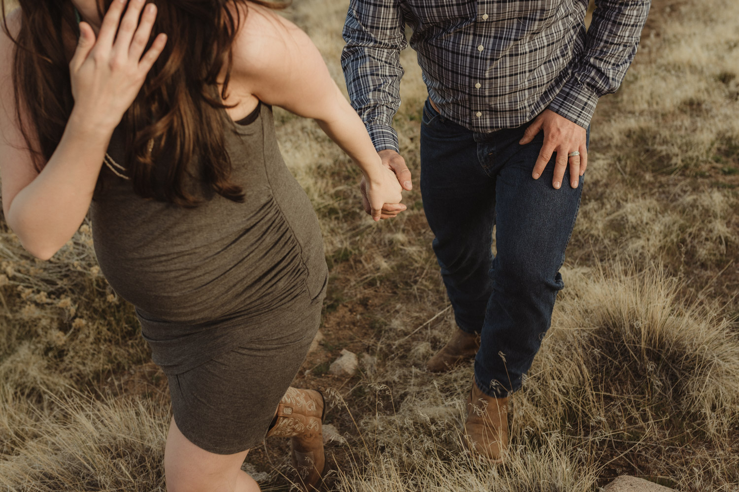 Desert maternity session couple hiking up a hill photo