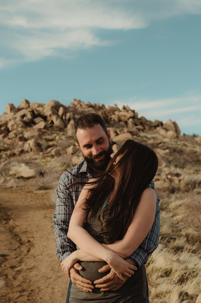 Desert maternity session couple laughing together photo