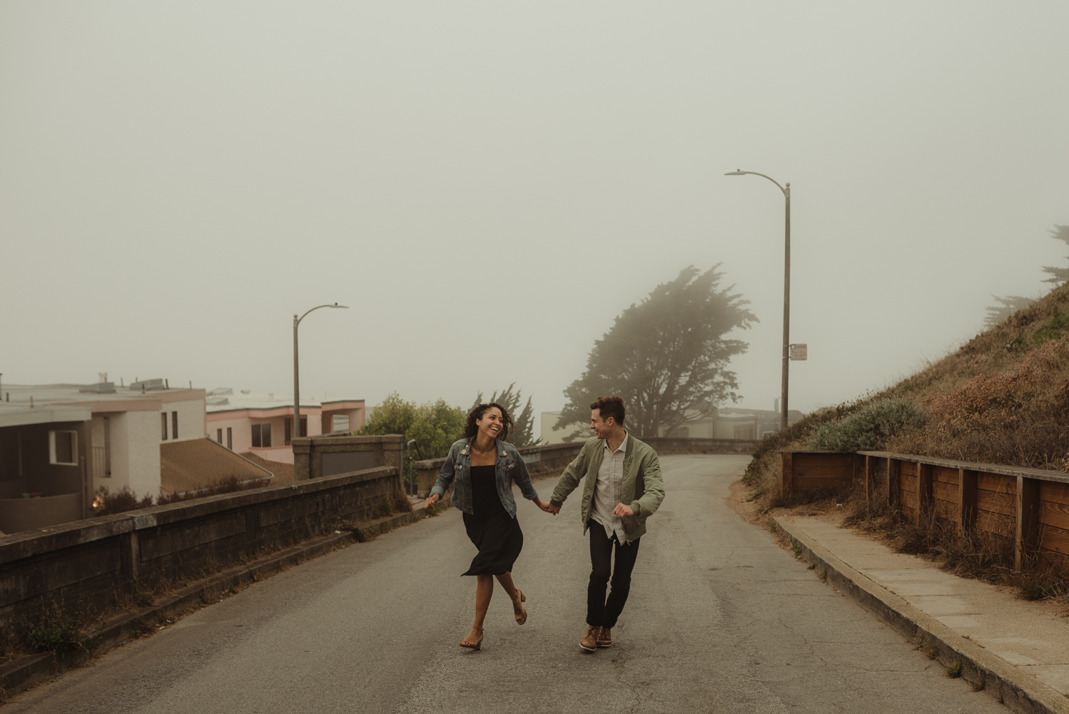 San Francisco foggy engagement session couple running in the fog photo