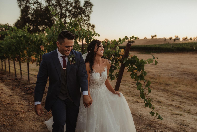 Rancho Victoria Vineyards wedding couple walking through the vineyard photo
