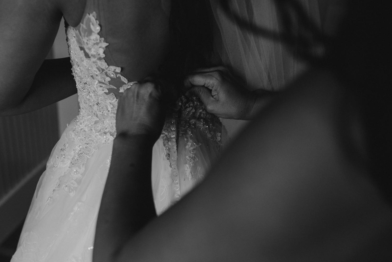 Rancho Victoria Vineyards wedding bride putting on her wedding dress photo