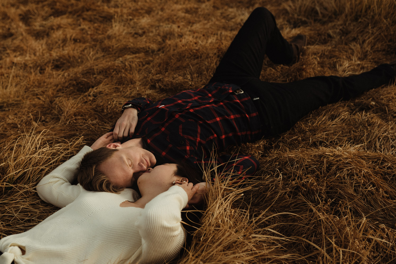 Tahoe meadows interpretive loop romantic sunrise session couple laying on the dry grass photo