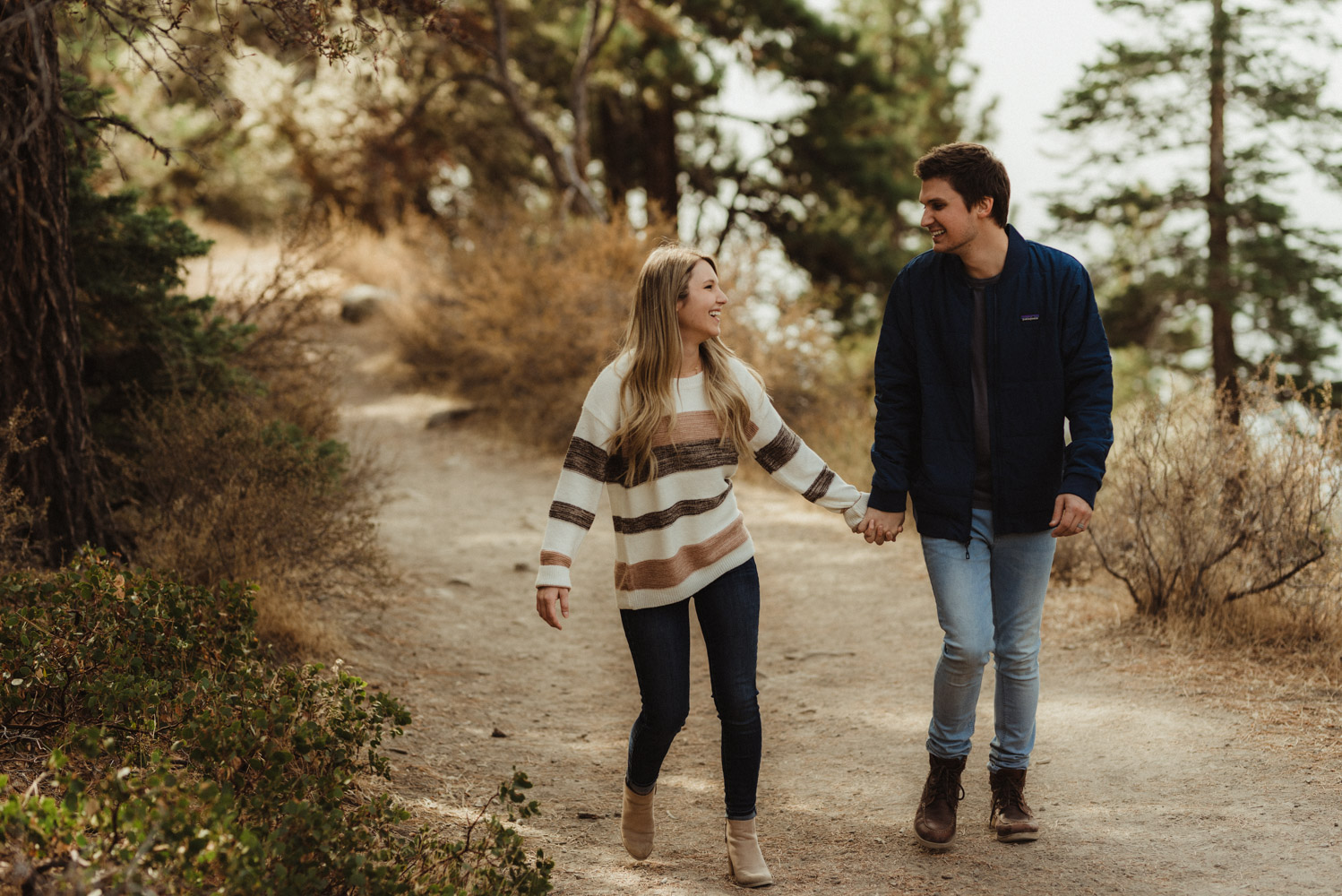 Cave Rock engagement session inspiration at Lake Tahoe,  couple walking in the forest photo
