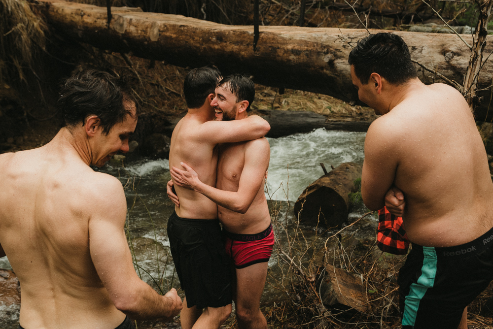 Twenty Mile House Wedding in April, groomsmen taking a dip in the river and hugging photo