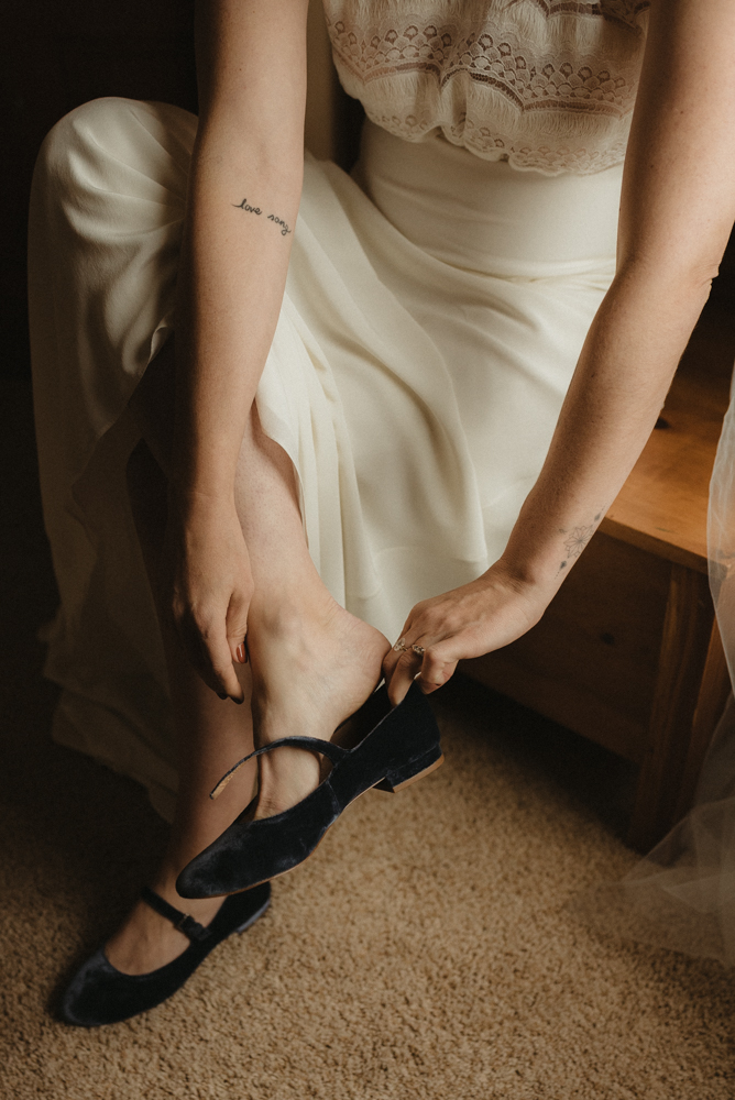 twenty mile house wedding, bride putting on her shoes photo