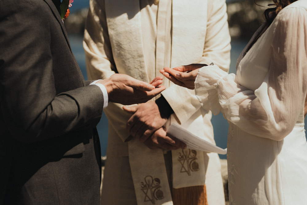 Emerald Bay Elopement, bride and groom holding rings photo