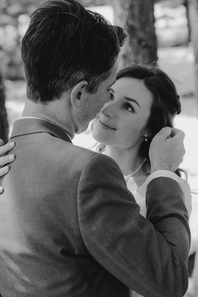 Emerald Bay Elopement in April, groom playing with brides hair photo