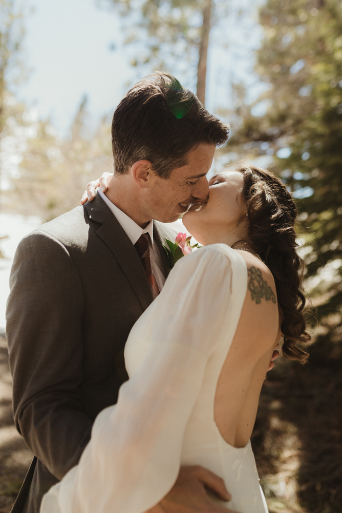 Emerald Bay Elopement in April, couple kissing in the tahoe forest photo