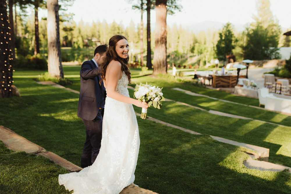 Martis Camp Wedding, couple walking and bride looking at the camera photo