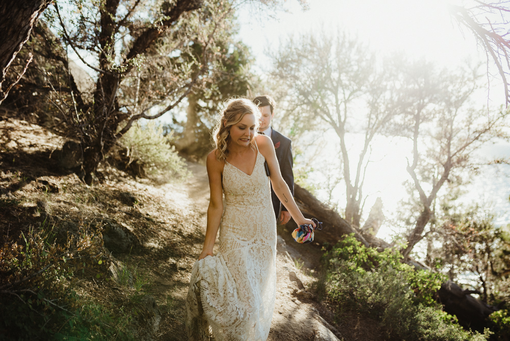 Lake Tahoe Elopement, photo of couple walking on a trail with dust and sun