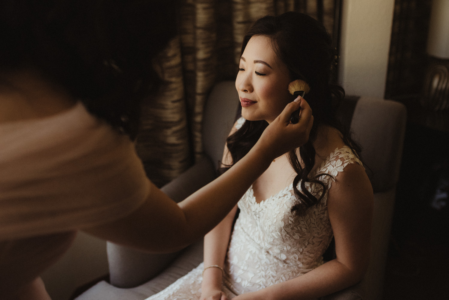 Hellman-Erman Mansion Wedding, photo of bride getting her makeup done by her sister