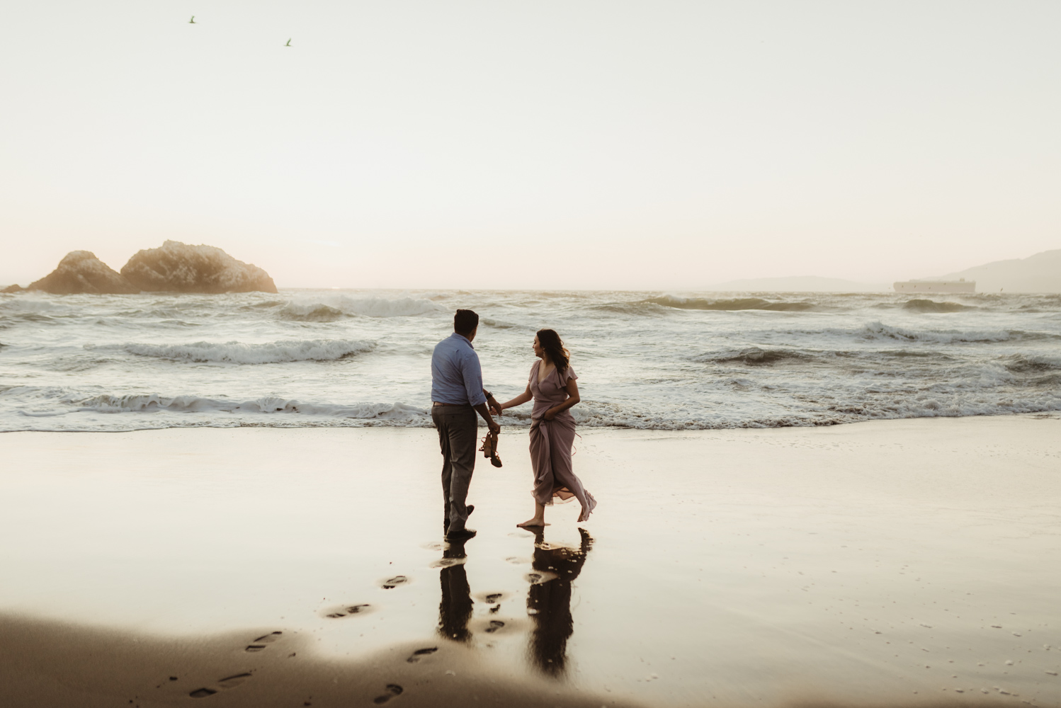 Sutro Baths Engagement Session, couple holding hands by the beach