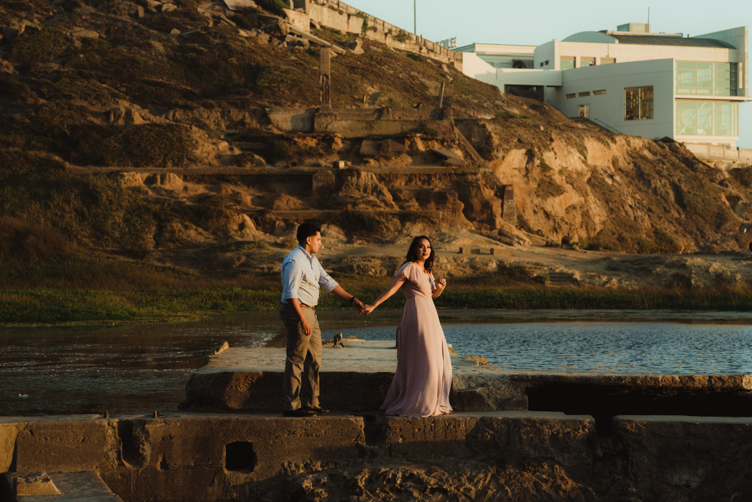 Sutro Baths Engagement Session, photo of couple holding hands with the ocean in the background