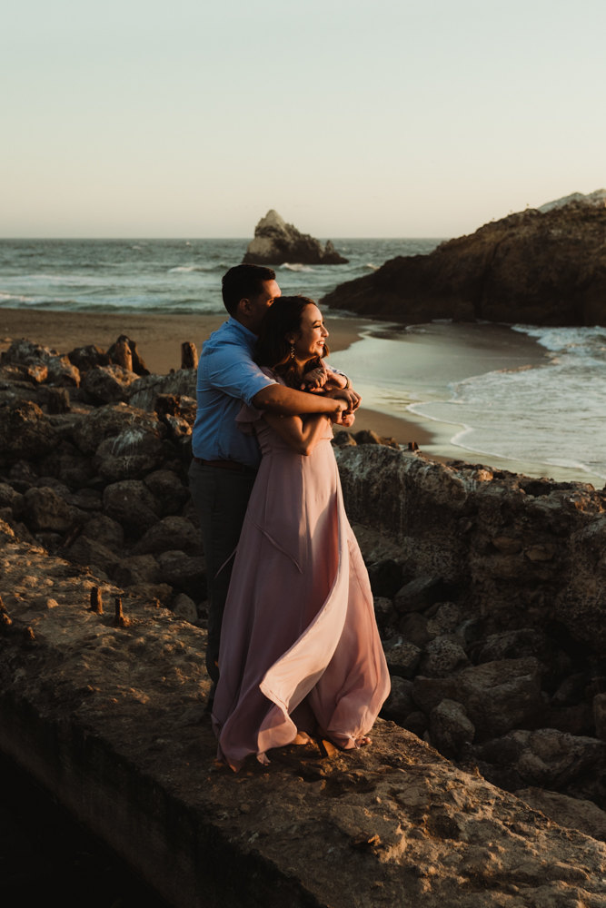 Sutro Baths Engagement Session, photo of couple laughing and looking toward the sunset